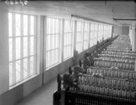 18961 FDHEEMAF057236 Batterij ringspinmachines van de Koninklijke Nederlandse Katoen Spinnerij (KNKS) te Hengelo met op ...