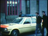 5022 BB07712 Een film met beelden van:- Een politieauto, agenten en twee arrestanten;- De twee worden het politiebureau ...