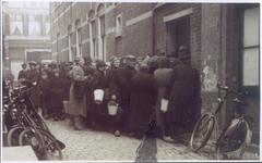 19762 FD029434 Mensen staan bij de ingang van slagerij Spruit in de binnenstad van Zwolle te wachten op een portie ...