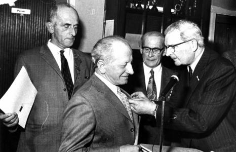 90656 Afbeelding van de uitreiking van een onderscheiding door burgemeester J. van der Heide (rechts) van de gemeente ...