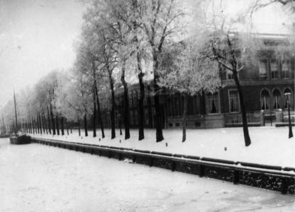 69741 Gezicht vanaf de Willemsbrug op de dichtgevroren Stadsbuitengracht en de huizen aan de besneeuwde Rijnkade te Utrecht.