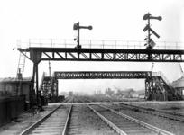 163644 Gezicht op de spoorwegovergang en de voetgangersbrug richting het Mariniersplein te Amsterdam, ter hoogte van de ...