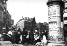 72582 Gezicht op de noordoosthoek van de Neude te Utrecht tijdens de warenmarkt; rechts een reclamezuil (Litfasssäule) ...