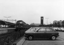 154556 Gezicht op de P+R-parkeerplaats bij het N.S.-station Nijmegen te Nijmegen met links langs het perron de trein ...