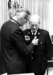 90572 Afbeelding van de uitreiking van een koninklijke onderscheiding door burgemeester J. van der Heiden van de ...
