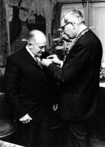 90655 Afbeelding van de uitreiking van een koninklijke onderscheiding door burgemeester J. van der Heide van de ...