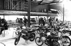 90464 Afbeelding van de controle door de Rijkspolitie van mogelijk opgevoerde bromfietsen in de werkplaats van de ...