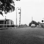 166537 Gezicht op de spoorwegovergang in de Schaikseweg / Spoorstraat te Leerdam, met links overwegpost Post I.