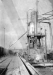 167004 Afbeelding van het overladen graan van schip naar trein via een elevator in de haven van Rotterdam.