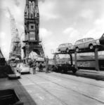 167038 Afbeelding van het overladen van personenauto's (Ford Anglia's) van een schip naar trein (dubbeldeks ...