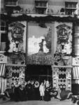 400533 Afbeelding van een groepje vrouwen in Zeeuwse klederdracht bij de versierde voorgevel van het ...