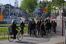827702 Afbeelding van wachtende fietsers bij het verkeerslicht voor het fietspad op de hoek van het Paardenveld en de ...