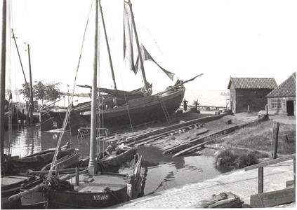 WAT006002289 De scheepswerf van Jan Hoogland In de haven de VD168 zo te zien een ijzeren botter, na 1936 gebouwd. De ...