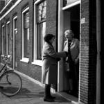 RJ000000056 Pannetjes met warm eten wordt aangereikt door een UVV medewerkster aan een oudere dame in het kader van ...