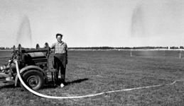 RJ000000928 Veehouder P. W. Grotendorst bij de pomp die woensdagmorgen door de B.B. op zijn land in de Beemster werd ...
