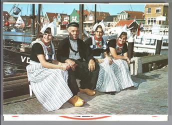 WAT001013293 Ansichtkaart van drie Volendamse dames en een oude Volendamse man. Ze zitten samen in de haven.