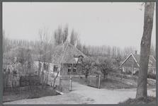 WAT001000257 Stolpboerderij aan de Oostdijk nummer 27.Rechts zien we een woning aan de Oostdijk nummer 25.