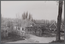 WAT001000266 Stolpboerderij aan de Oostdijk nummer 27.Rechts daarnaast zien we een huis op Oostdijk nummer 25.