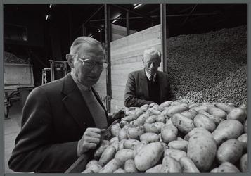 WAT001000539 Deze twee heren keuren een partij aardappels.