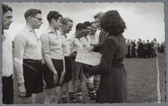 WAT001005033 Sport uitwisseling met Arendonck België 1948.M.v. Glandorf-Groot reikt hier iets uit aan de Arendonckspelers.