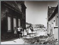 WAT001010420 Wijdesteeg. Melkboer Smit in de deuropening.Meisjes lopen door de opengebroken straat.