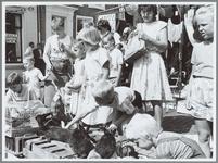 WAT001016200 Zomerdrukte tijdens veemarkt op Pinkster drie. Kinderen spelen met konijntjes.