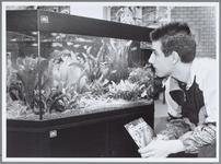 WAT001016377 Raymond Wisman kijkt geboeid naar been aquarium met vissen. Expositie aquavo.