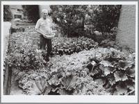 WAT001016420 Deze man heeft zijn voortuin omgevormd tot groentetuin.En nu is het tijd om te oogsten.