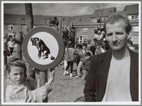 WAT001016553 Herman Klepper naast hondepoepbord op een speelplaats.