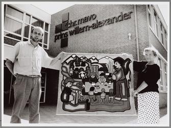 WAT001016571 Foto: Rosa Wals en mavo-docent Bert Post tonen het Chileense wandkleed uit Linares.In de-Prins Willem ...