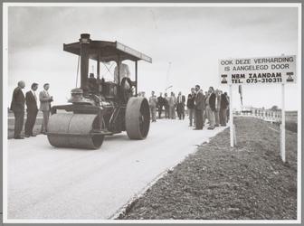 WAT001017173 Foto: Milieugedeputeerde G. de Boer walst met een Engelse 'Marshall' stoomwals de werkweg naar de ...