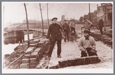 WAT002000135 Stratenmakers op de zandweg met in het verschiet de molen De Veerschuit en op de hoek de tabakszaak van ...
