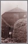 WAT002001505 George Johannes de Vries rechts boven op de hooiberg van boerderij naast gemeentehuis, met helper buurman ...