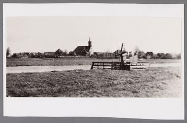 WAT002001724 Gezicht op de hervormde kerk met vooraan pet/ watermolentje op land, 'De slijpmolen' van Jan Vink. ...