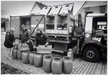 WAT003002783 Bewoners leveren chemisch afval in bij een medewerker van de Chemokar.Op de achtergrond: sociaal cultureel ...