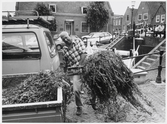 WAT003002958 Foto: Om de paar weken haalt een gemeentewerker rotzooi uit de sluis bij de Middendam in Monnickendam. De ...