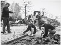 WAT003003209 Foto: Straatmaker A. Gase (met stok) en zijn medewerkers aan het werk in Amsterdam. Op de achtergrond de ...