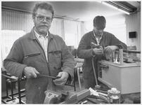 WAT003003199 Foto: Piet Wiersma (links) werkt tezamen met zijn assistent Jeroen van Craaykamp in de werkplaats aan de ...