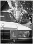 WAT003003215 Foto: instructeur Ed Brink van 'Rijschool Brink' bij zijn wagen.Hij vierde zijn 25 jarig jubileum.