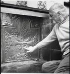 WAT003003513 Foto: Ernst Rijswijk de vroegere dorpssmid wijst trots op de schoorsteenplaat met de tekst pax Avrea, een ...