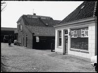 WAT003003867 Links een stal en rechts de kruidenierswinkel.