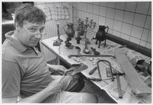 WAT003003904 Foto: Tingieter Erik Blaauboer aan zijn werktafel, met links enkele producten van zijn hand. (informatie: ...