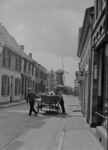 107 Wijhe: Opname van een paard met wagen in de Langstraat, met huizen en een molen op de achtergrond, dit is de ...