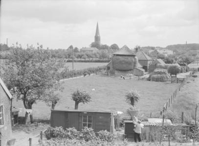 108 Wijhe: Opname vanaf een hoogte van het dorp, met de kerk op de achtergrond, en een hooischuur in beeld., 1938-06-29