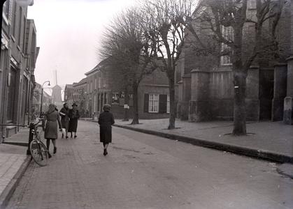 114 Wijhe: Opname van een straat in het dorp met voetgangers, een gedeelte van een kerk in beeld en een molen op de ...
