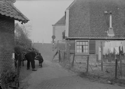 115 Wijhe: Opname van een man met kind op een erf tussen een paar huizen., 1941-02-12
