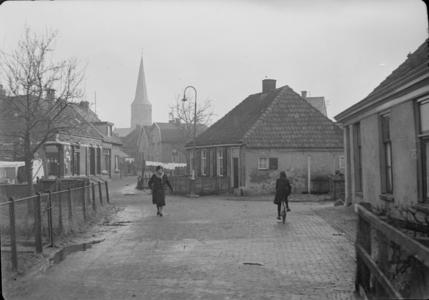 116 Wijhe: Opname van een straat in het dorp, met huizen, een voetganger en een fietser en een kerktoren op de ...