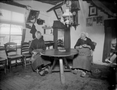 76 Markelo: opname van het interieur van leemboerderij 'De Eikenhof', met twee vrouwen die verstelwerk doen., 1935-10-25