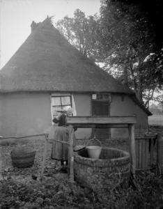 77 Markelo: Opname van een Twentse boerin bij een waterpomp, 1935-10-25