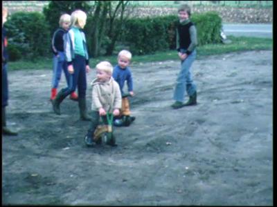 13867 BB00326 Familiefilm Olthof.Een groep kleine kinderen speelt op een drassig veldje in de straat. Ze poseren en ...